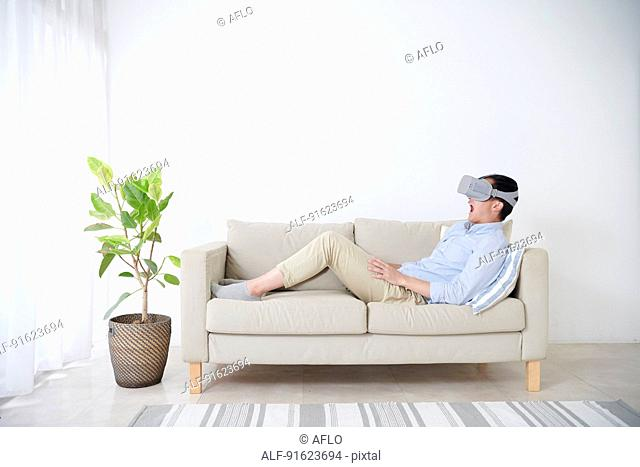 Young Japanese man using VR goggles
