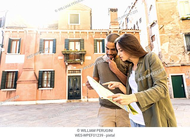 Italy, Venice, young couple looking at map in the city
