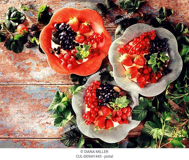 Fruit desserts, with mixed berries, on rustic wooden table, overhead view