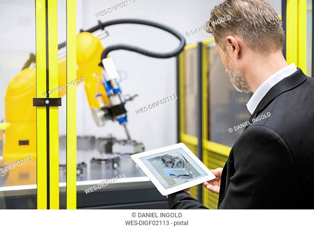Mature businessman controlling industrial robots with digital tablet