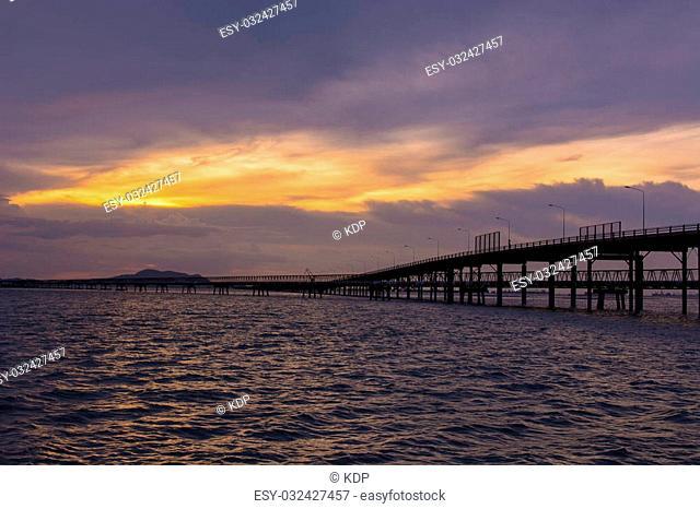 Bridge across the sea and sunset scene