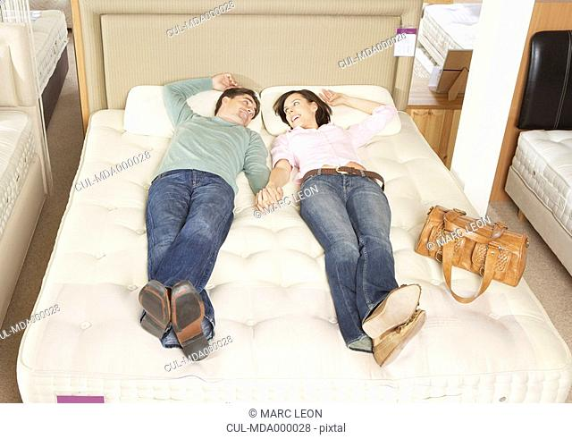 Couple lying on bed in furniture store