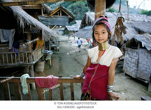 A young Longneck girl on a porch overlooking the street Approximately 300 Burmese refugees in Thailand are members of the indigenous group known as the...
