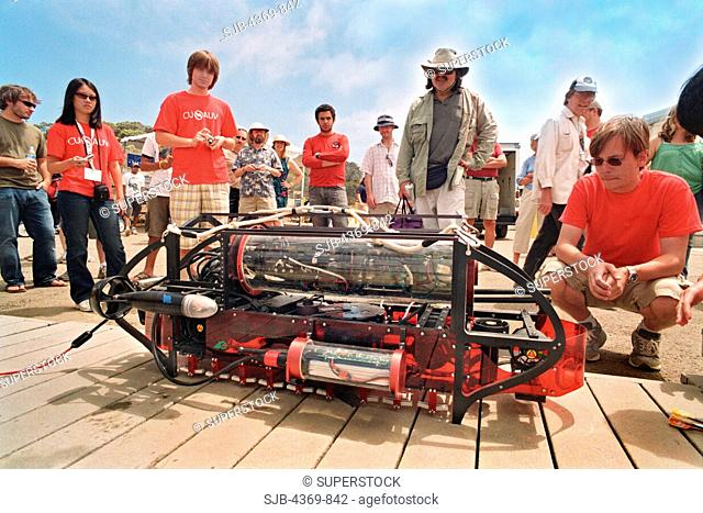 The Cornell University's 'Nova' 2009 Autonomous Underwater Vehicle AUV, about to be weighed and hoisted into the water. Red-shirted team-mates guard it like...