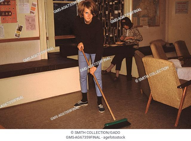 Vernacular snapshot photograph of woman sweeping the floor of a youth hostel, 1961