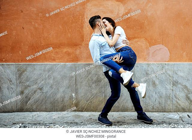 Carefree couple in love in front of a wall outdoors