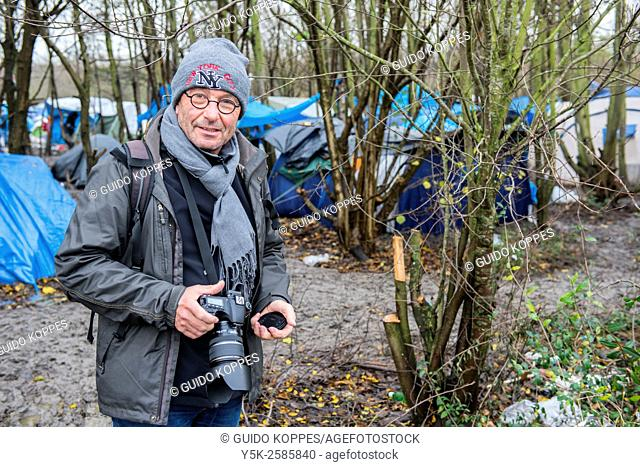 Dunkerque, France. Male photographer working in a camp for illegal migrants, bound for the UK