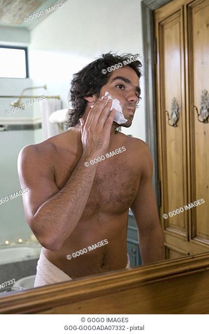 Man spreading shaving cream on face