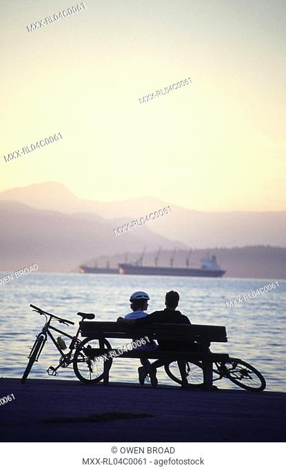 Silhouette of couple sitting on bench with bikes at Kit's Beach, Vancouver, BC, Canada