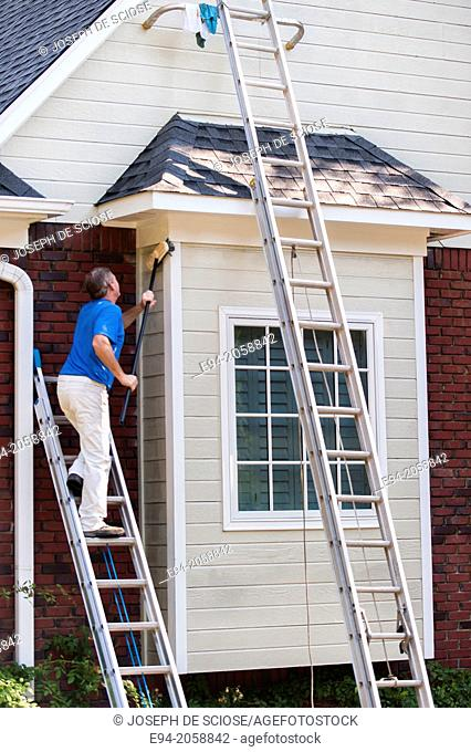 A 45 year old man on a ladder cleaning the wood siding of a house with a brush
