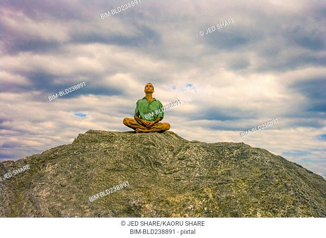 Man meditating on rock under clouds