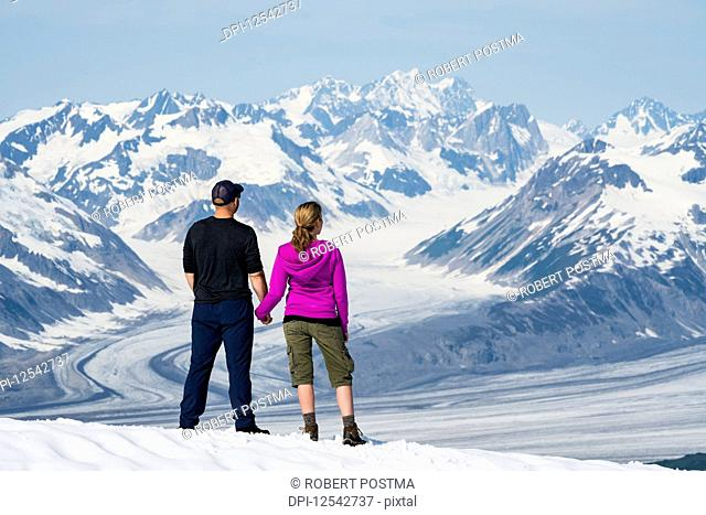A couple enjoy the sights and scenery of Kluane National Park and Reserve on a bright sunny day; Haines Junction, Yukon, Canada