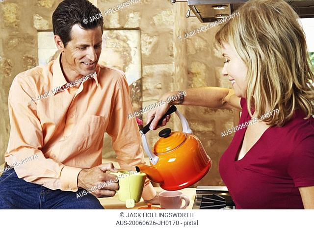 Mature man holding a cup with a mature woman pouring tea into it