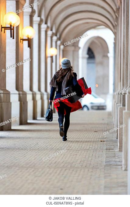 Rear view of mature woman with Christmas gift walking through city colonnade