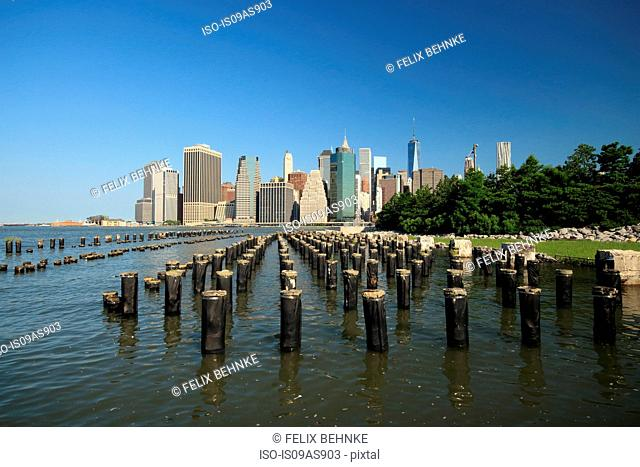 Wooden posts in river, cityscape behind, Manhattan, New York City, USA