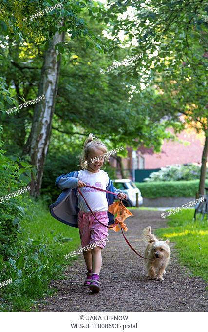 Little girl walking with her dog