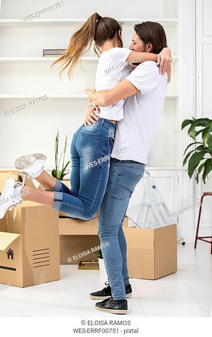 Happy couple with cardboard boxes hugging in new home