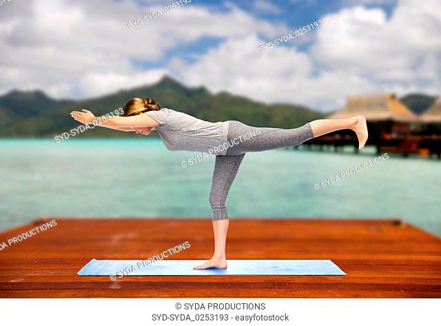 woman making yoga warrior pose on mat outdoors