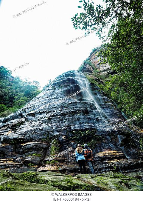 Australia, New South Wales, Blue Mountains National Park, Leura Cascades, Mid-adult couple at foot of rock with waterfall in forest