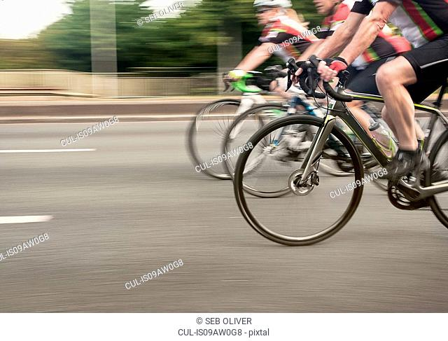 Neck down view of three cyclists speeding on urban road in racing cycle race