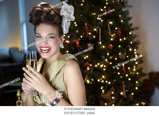 Portrait of happy stylish woman holding champagne glass at Christmas party