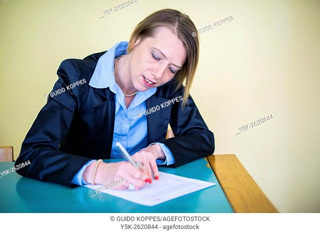 Tilburg, Netherlands. Attractive blonde woman signing a model release before a studio shoot