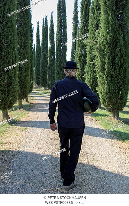 Italy, Tuscany, rear view of man surrounded by cypresses wearing a bowler hat holding a melon