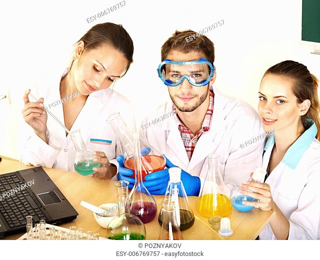 Group chemistry student with flask in classroom