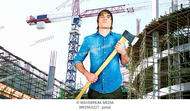 Confident hipster holding ax against incomplete buildings