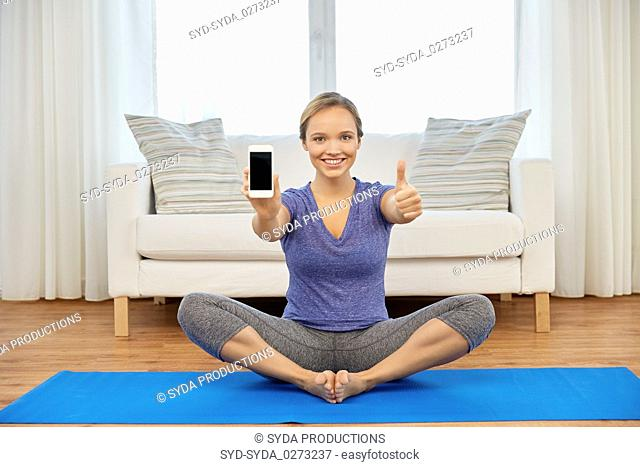 woman with smartphone doing yoga at home