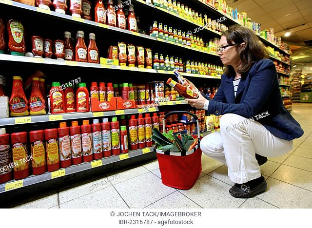 Woman shopping in a self-service grocery department, supermarket, Germany, Europe