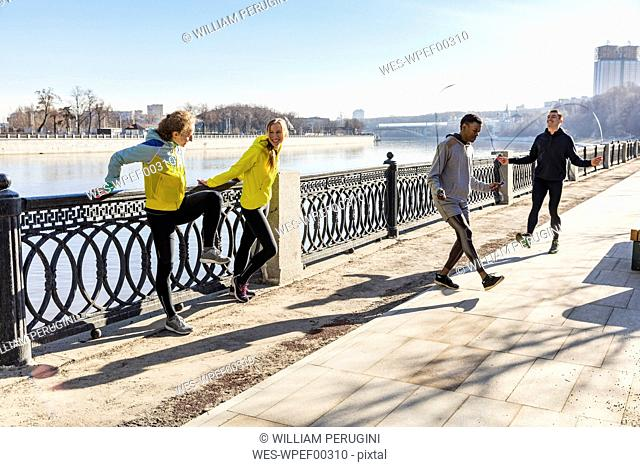 Friends exercising on waterfront promenade in the city