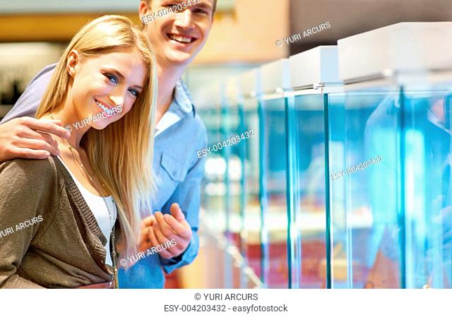 Lovely young couple standing in front of a jewellery display cabinet and smiling at the camera while holding hands - portrait