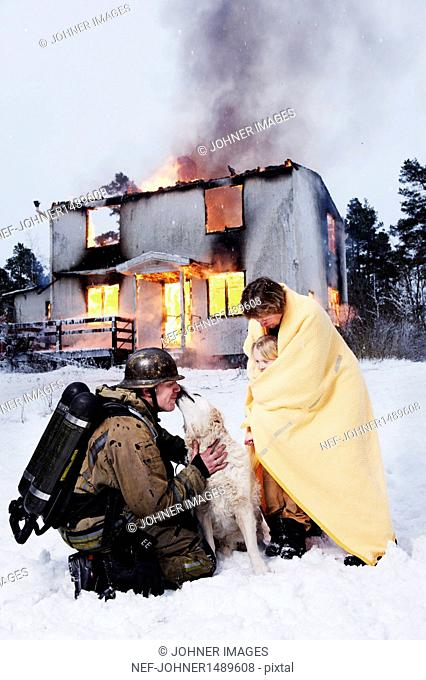 Fireman with rescued people and dog in front of burning house