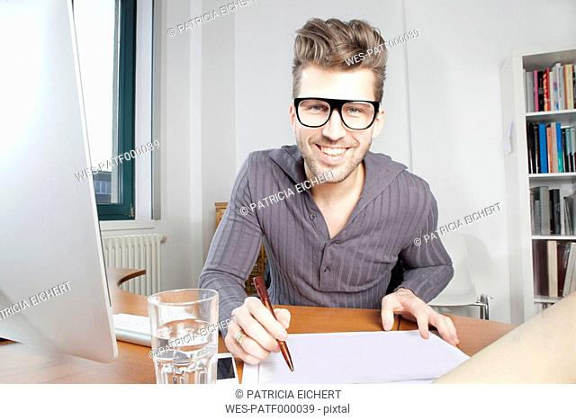 Portrait of smiling young man at desk in an office