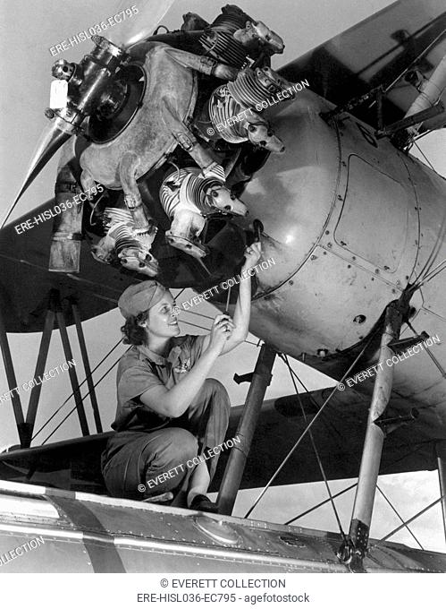 20 year old women and expert aviation mechanic working on a Wright Whirlwind airplane motor. She rebuilt the engine at a Naval Air Base, Oct. 1942