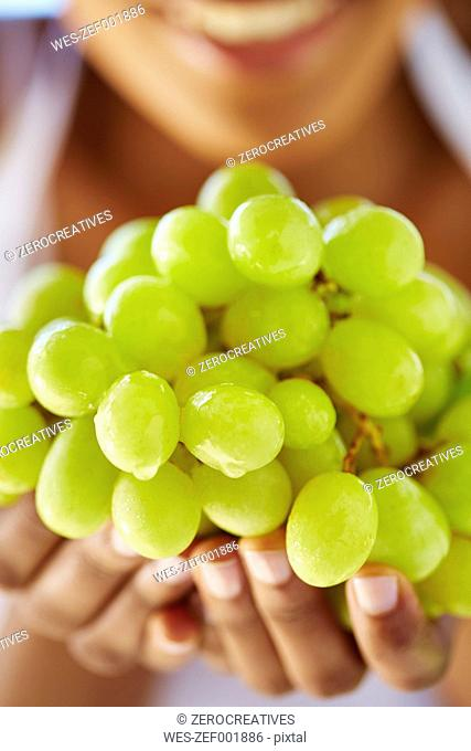 Woman's hands holding green grapes