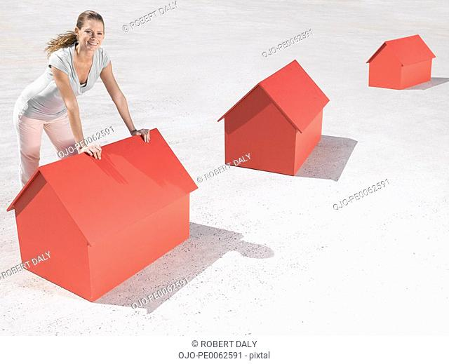 Woman leaning over model houses