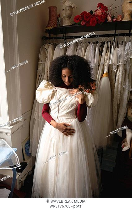 Young bride trying wedding dress from clothes hanger