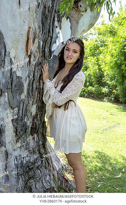 Eighteen year old girl standing near a tree, La Jolla, California