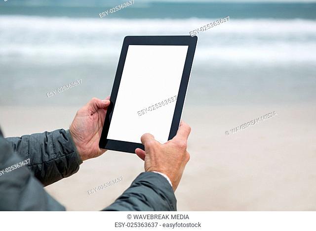 Man using digital tablet on beach