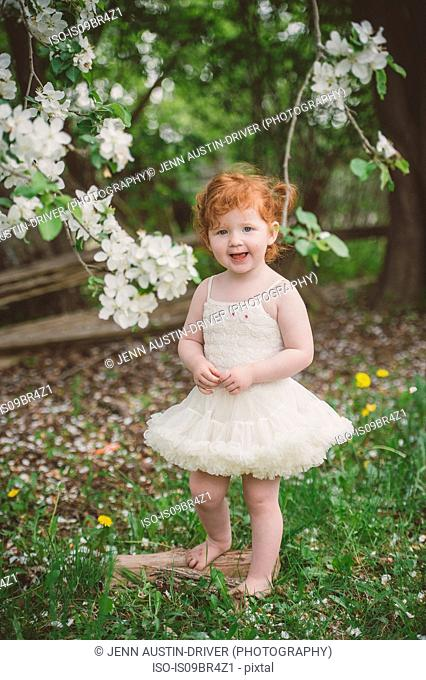Toddler in tutu by blossom tree