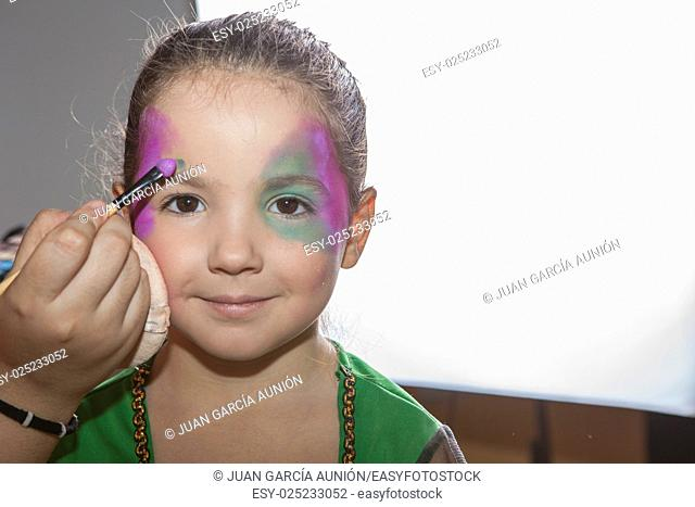 Little smiling girl making facepaint before halloween party. The make-up artist is applying some colors