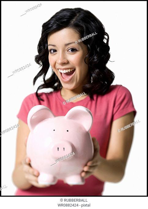 Portrait of a teenage girl holding a piggy bank