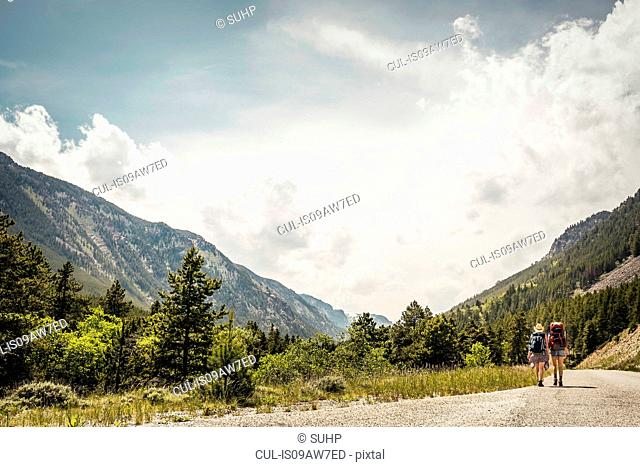 Rear view of young woman and teenage girl hiker hiking along rural road, Red Lodge, Montana, USA