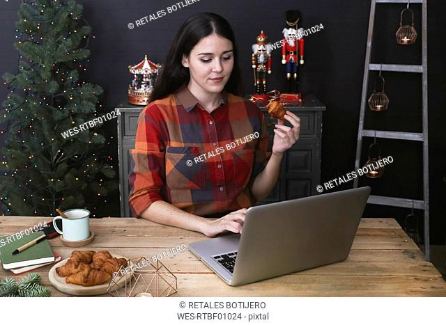Young woman using laptop while eating croissant at Christmas time