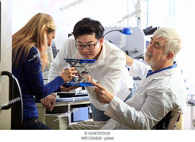 Professor with muscular dystrophy working with engineering students setting up adjustable stage at chemical analysis instrument in a laboratory