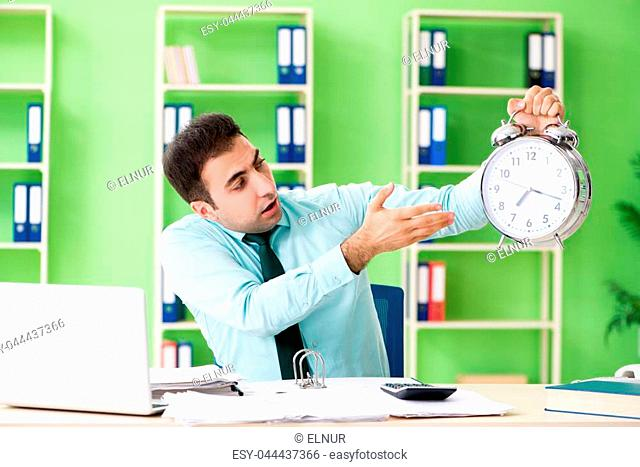 Male financial manager working in the office in time management concept