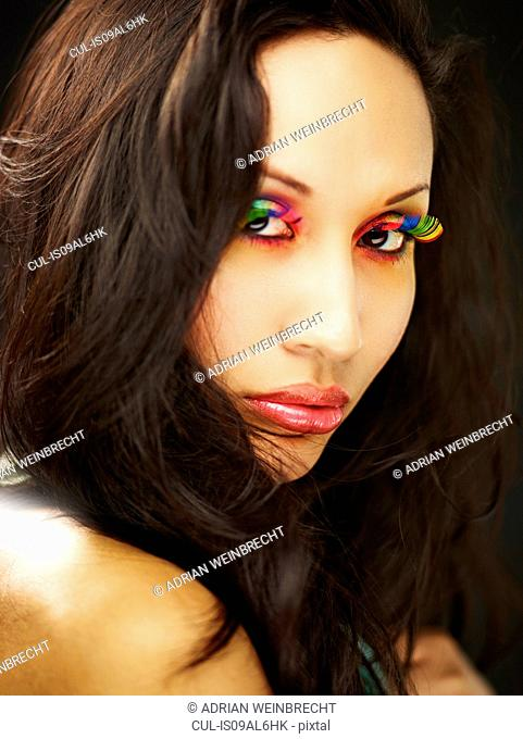 Young woman wearing rainbow coloured fake eyelashes