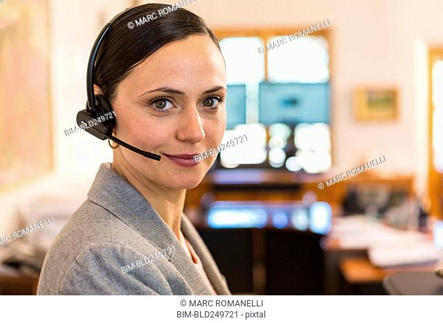 Portrait of smiling Caucasian businesswoman wearing headset